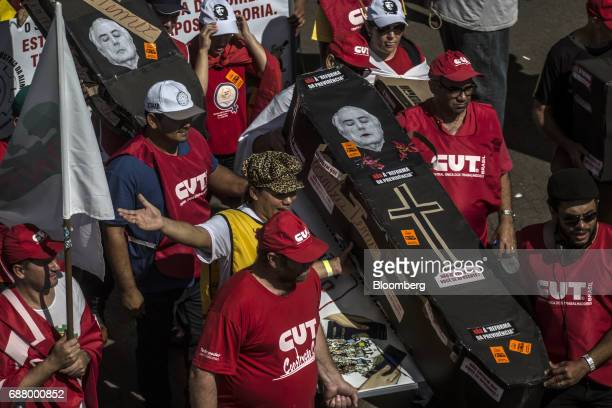 Demonstrators carry a mock coffin adorned with a photograph of Michel Temer president of Brazil during protests outside of the National Congress...
