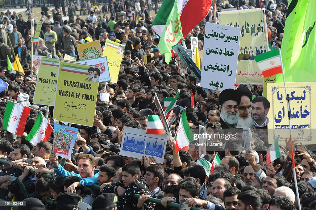 Demonstrators carry anti US, Israel and pro regime banners along with Iranian flags and photos of the leaders in Azadi square during the 34th anniversary of the Islamic revolution on February 10, 2013 in Tehran, Iran.