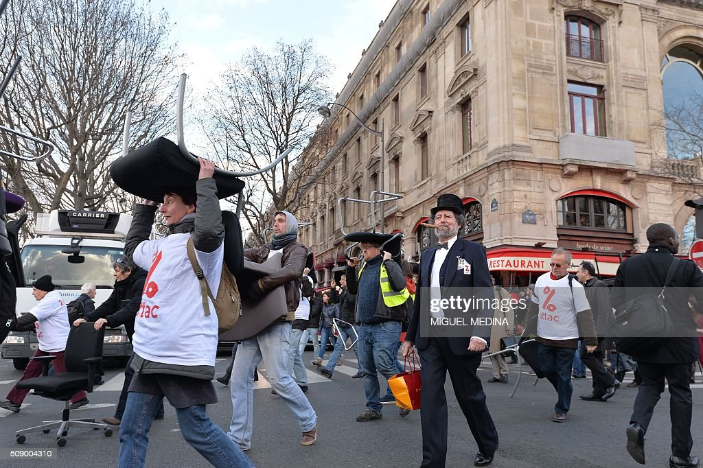 Demonstrators carry chairs on their head taken from bank offices on February 8, 2016 in the place du Chatelet in Paris during a demonstration against bank system and tax fraud, as former French budget minister Jerome Cahuzac goes on trial on February 8 for tax fraud. Cahuzac resigned in disgrace in 2013 after admitting to having a secret Swiss bank account, and faces up to seven years in jail and two million euros ($2.2 million) in fines. AFP PHOTO / MIGUEL MEDINA / AFP / MIGUEL MEDINA