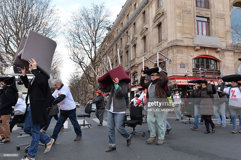 Demonstrators carry chairs on their head taken from bank offices on February 8, 2016 near the Court of Paris during a demonstration against bank system and tax fraud, as former French budget minister Jerome Cahuzac goes on trial on February 8 for tax fraud. Cahuzac resigned in disgrace in 2013 after admitting to having a secret Swiss bank account, and faces up to seven years in jail and two million euros ($2.2 million) in fines. AFP PHOTO / MIGUEL MEDINA / AFP / MIGUEL MEDINA
