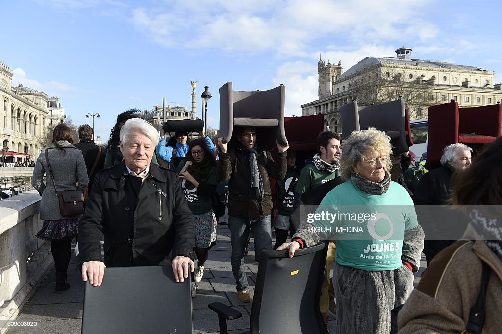 Demonstrators carry chairs taken from bank offices on February 8, 2016 in Paris during a demonstration against bank system and tax fraud, as former French budget minister Jerome Cahuzac goes on trial on February 8 for tax fraud. Cahuzac resigned in disgrace in 2013 after admitting to having a secret Swiss bank account, and faces up to seven years in jail and two million euros ($2.2 million) in fines. AFP PHOTO / MIGUEL MEDINA / AFP / MIGUEL MEDINA