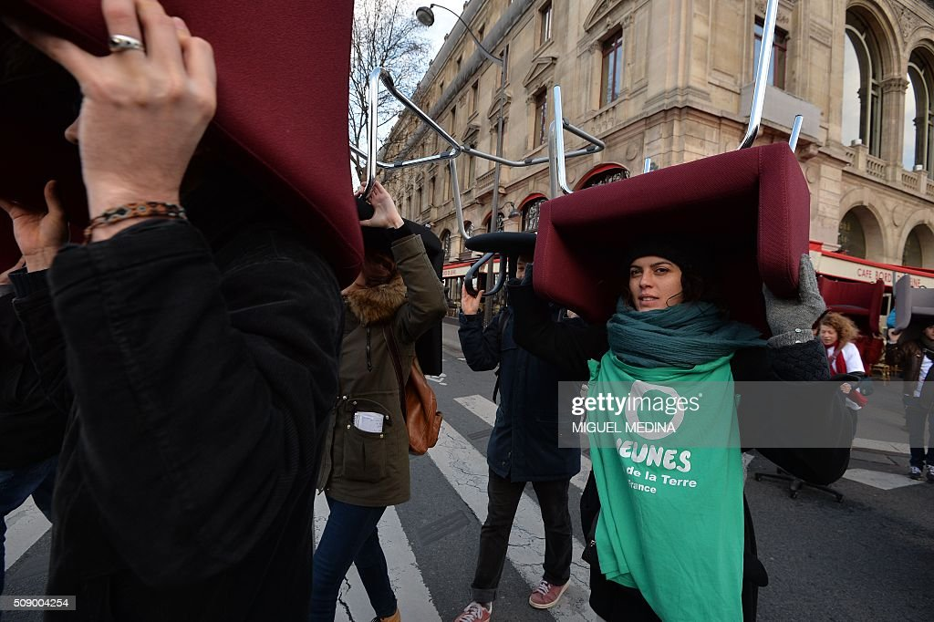 Demonstrators carry chairs taken from bank offices on February 8, 2016 in the place du Chatelet in Paris during a demonstration against bank system and tax fraud, as former French budget minister Jerome Cahuzac goes on trial on February 8 for tax fraud. Cahuzac resigned in disgrace in 2013 after admitting to having a secret Swiss bank account, and faces up to seven years in jail and two million euros ($2.2 million) in fines. AFP PHOTO / MIGUEL MEDINA / AFP / MIGUEL MEDINA