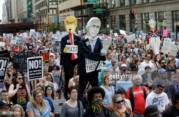 Demonstrators carry effigies of President Donald Trump and Vice President Mike Pence during a protest against hate white supremacy groups on Sunday...