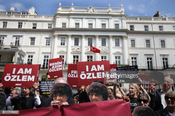 Demonstrators carry masks of global civic organisation Avaaz staffer Özlem Dalkran as they call for his release and all human rights defenders...