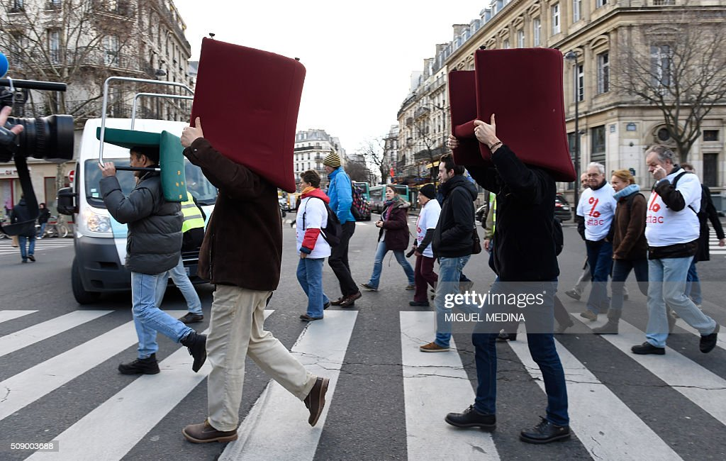 Demonstrators carry on their head chairs taken from bank offices on February 8, 2016 in Paris during a demonstration against bank system and tax fraud, as former French budget minister Jerome Cahuzac goes on trial on February 8 for tax fraud. Cahuzac resigned in disgrace in 2013 after admitting to having a secret Swiss bank account, and faces up to seven years in jail and two million euros ($2.2 million) in fines. AFP PHOTO / MIGUEL MEDINA / AFP / MIGUEL MEDINA