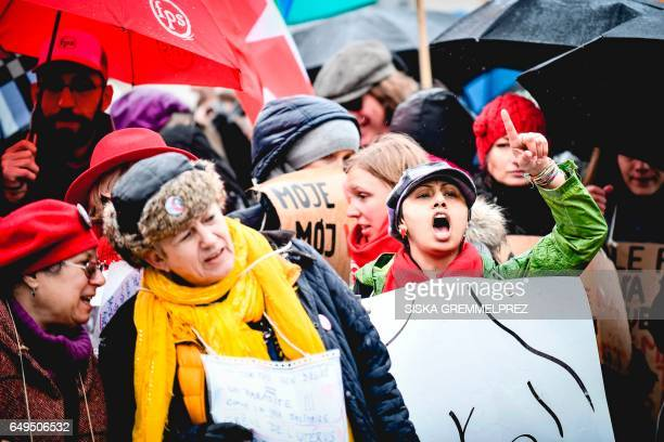 Demonstrators carry placards and shout slogans during an International Women's Day protest on March 8 2017 in Brussels / AFP PHOTO / BELGA / SISKA...