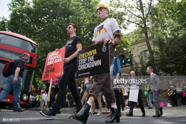 Demonstrators carry placards as they protest over an alleged crackdown on gay men in Chechnya outside the Russian Embassy in London on June 2 2017...