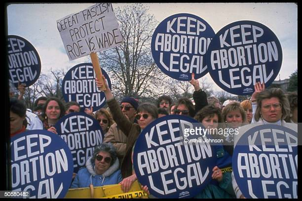 Demonstrators carrying giant keep abortion legal buttons protect Roe vs Wade sign during huge prochoice march