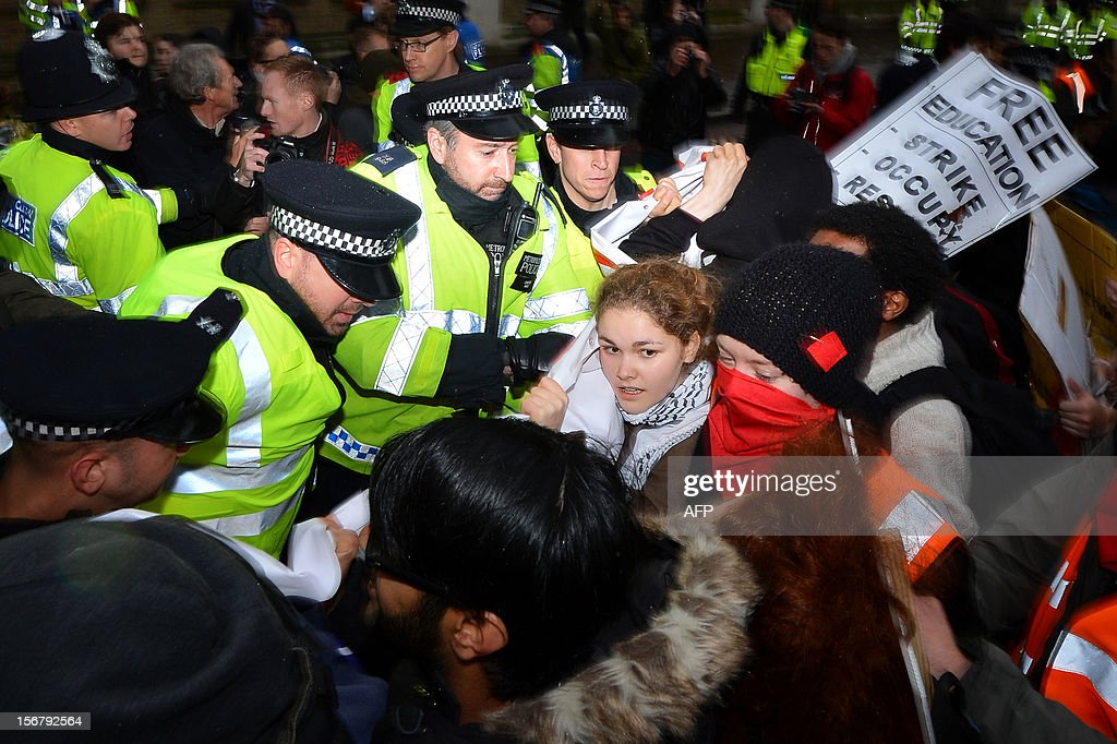 Demonstrators clash with police officers during a student rally in central London on November 21, 2012 against sharp rises in university tuition fees, funding cuts and high youth unemployment. AFP PHOTO/BEN STANSALL