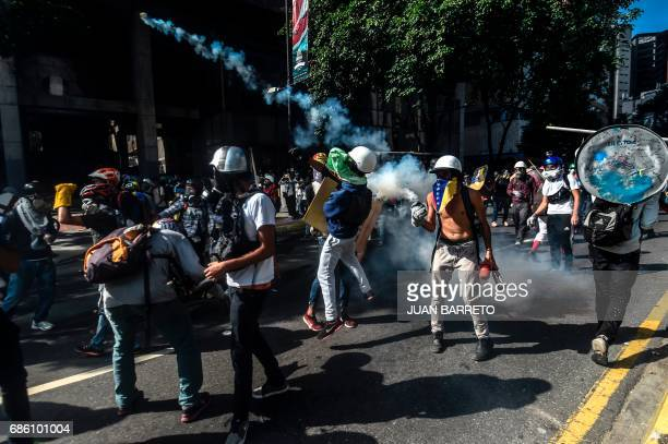 TOPSHOT Demonstrators clash with riot police during a protest against the government of President Nicolas Maduro in Caracas on May 20 2017 Venezuelan...