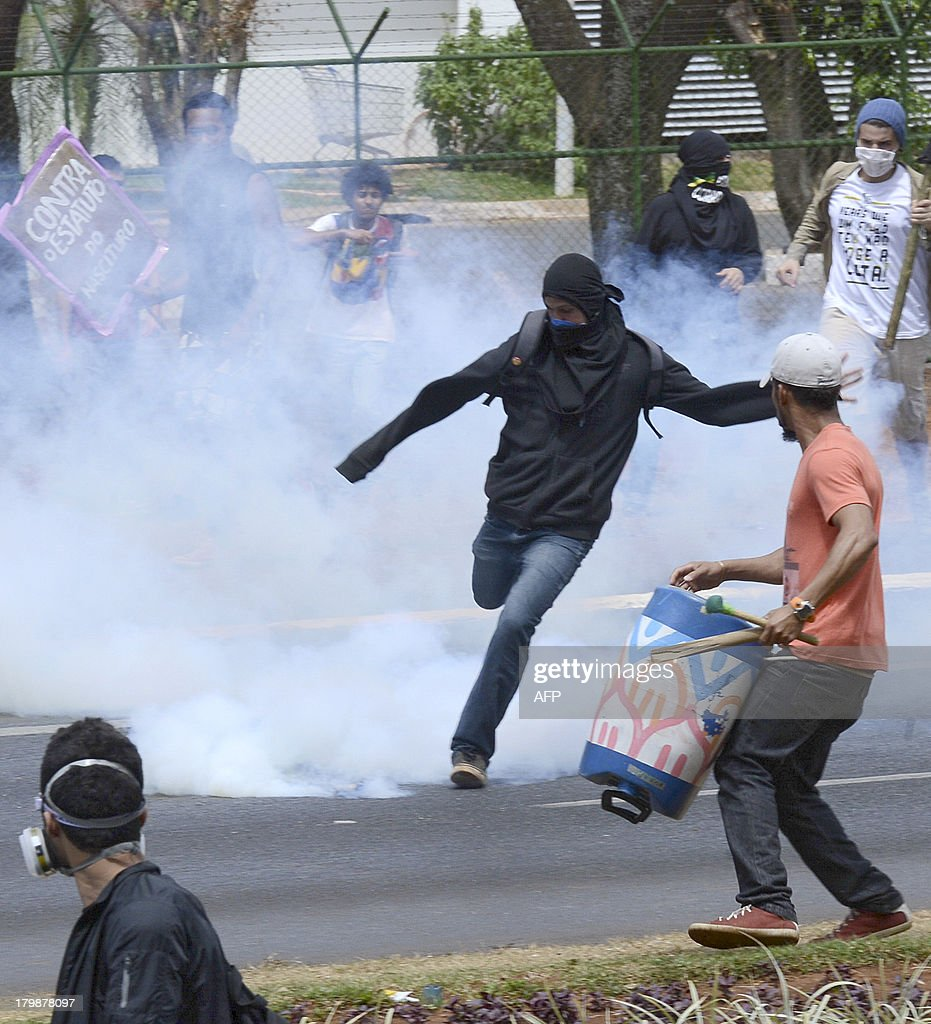 Demonstrators clash with riot police near the National stadium in Brasilia on September 07, 2013. More than 100 protesters interrupted a military parade in Rio Saturday held to mark Brazil's independence day and were dispersed with teargas. The protest, one of a series of demonstrations planned Saturday across the country, comes with Brazil in the international spotlight as it prepares to host the football World Cup next year.