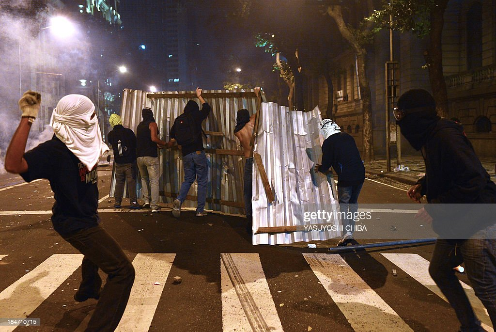 Demonstrators clash with the police during the 'Teachers' day' protest in demand of better working conditions and against police violence, on October 15, 2013 in Rio de Janeiro, Brazil.