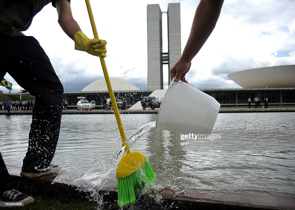 Demonstrators clean the sidewalk in front of the Brazilian National Congress, in Brasilia, on January 30, 2013 during a demonstration called by Rio de Janeiro's 'River of Peace' Movement symbolizing the need for 'cleaning' the senate of corruption. This week the presidential election will be held in the federal senate and the favorite candidate, senator Renan Calheiros, has been the target of many accusations of corruption.