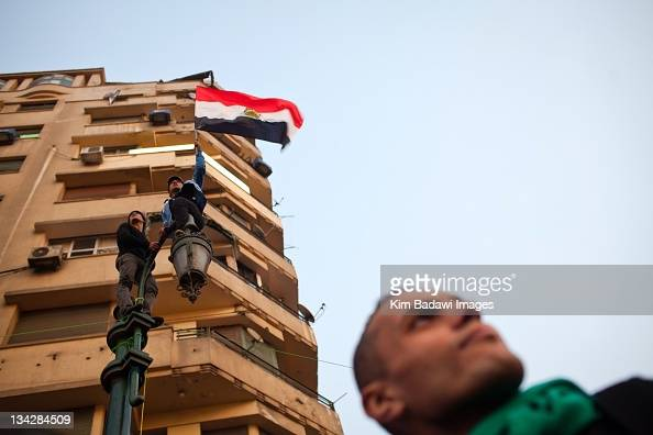 Demonstrators climb a lamp post on Tahrir Square off Mohamed Mahmoud in downtown Cairo on November 26 2011 in Cairo Egypt