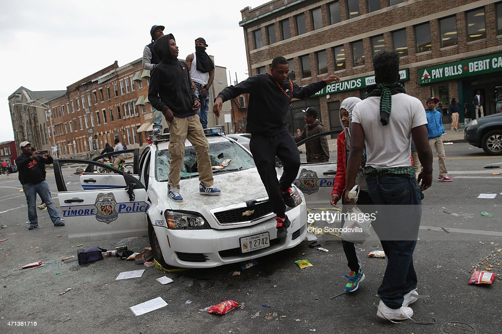 Demonstrators climb on a destroyed Baltimore Police car in the street near the corner of Pennsylvania and North avenues during violent protests...