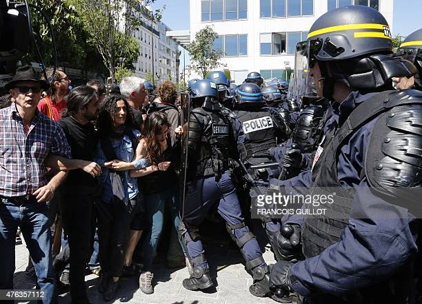 Demonstrators clung to each other are pushed away by the police during a migrants evacuation operation on June 8 2015 in front of the Vaclav Havel...