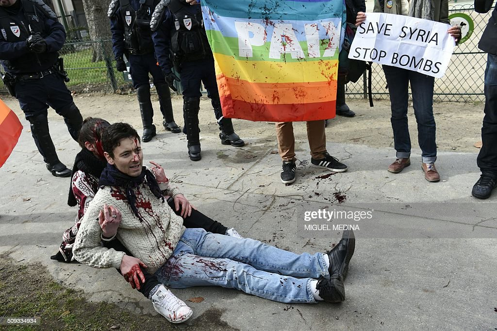 Demonstrators covered in fake blood sit on the sidewalk during a protest in front of the Russian Embassy in Paris on February 10, 2016 to demand a stop to the bombardment of Aleppo and an alternative peace plan for the conflict in Syria. / AFP / MIGUEL MEDINA