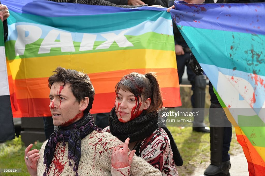 Demonstrators covered in fake blood sit on the sidewalk in front of rainbow flags reading 'Peace' during a protest in front of the Russian Embassy in Paris on February 10, 2016 to demand a stop to the bombardment of Aleppo and an alternative peace plan for the conflict in Syria. / AFP / MIGUEL MEDINA