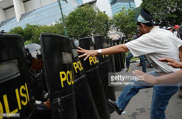 Demonstrators demanding the president reelection clash with Indonesian police during a riot simulation in Jakarta Indonesia on July 19 2014 The...