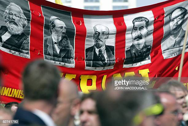 Demonstrators display a banner featuring communist greats Karl Marx Friedrich Engels Lenin Stalin and Mao Zedong during a May Day procession at...