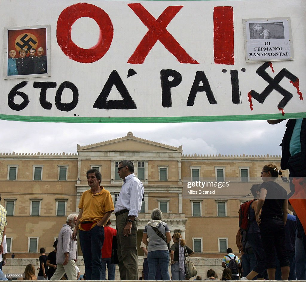 Demonstrators display a banner that reads ' NO to the 4th Reich' prior to a protest against the visit to Greece by Germany's Chancellor <a gi-track='captionPersonalityLinkClicked' href=/galleries/search?phrase=Angela+Merkel&family=editorial&specificpeople=202161 ng-click='$event.stopPropagation()'>Angela Merkel</a> on October 9, 2012 in Athens, Greece. Germany's Chancellor <a gi-track='captionPersonalityLinkClicked' href=/galleries/search?phrase=Angela+Merkel&family=editorial&specificpeople=202161 ng-click='$event.stopPropagation()'>Angela Merkel</a> arrived in Greece on her first visit since Europe's debt crisis erupted here three years ago, braving protests to deliver a message of support to a nation hammered by recession and fighting to stay in the euro.