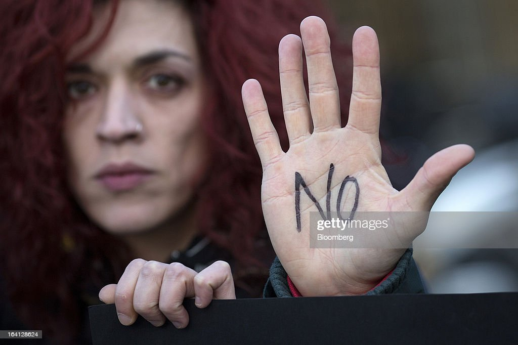 Demonstrators display 'No' signs on their hands during a protest outside the parliament against bank deposit tax plans in Nicosia, Cyprus, on Tuesday, March 19, 2013. Euro-area finance ministers told Cyprus to raise 5.8 billion euros ($7.5 billion) from bank depositors to unlock emergency loans, maintaining the revenue target while suggesting sparing small-scale savers. Photographer: Simon Dawson/Bloomberg via Getty Images