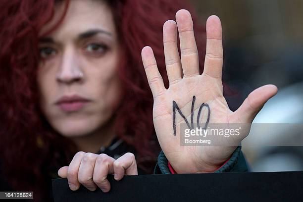 Demonstrators display 'No' signs on their hands during a protest outside the parliament against bank deposit tax plans in Nicosia Cyprus on Tuesday...