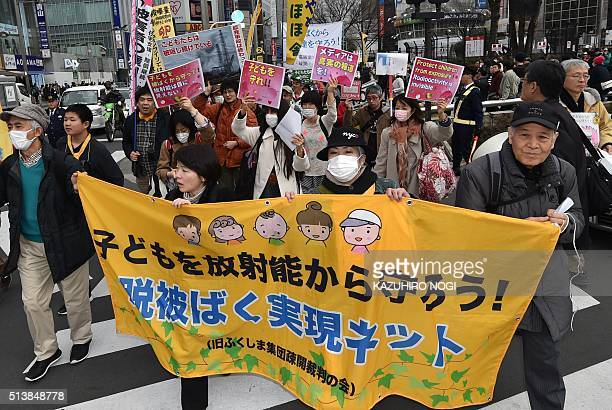 Demonstrators display placards calling on the government to protect children against radiotion during an antinuclear protest in Tokyo on March 5 2016...