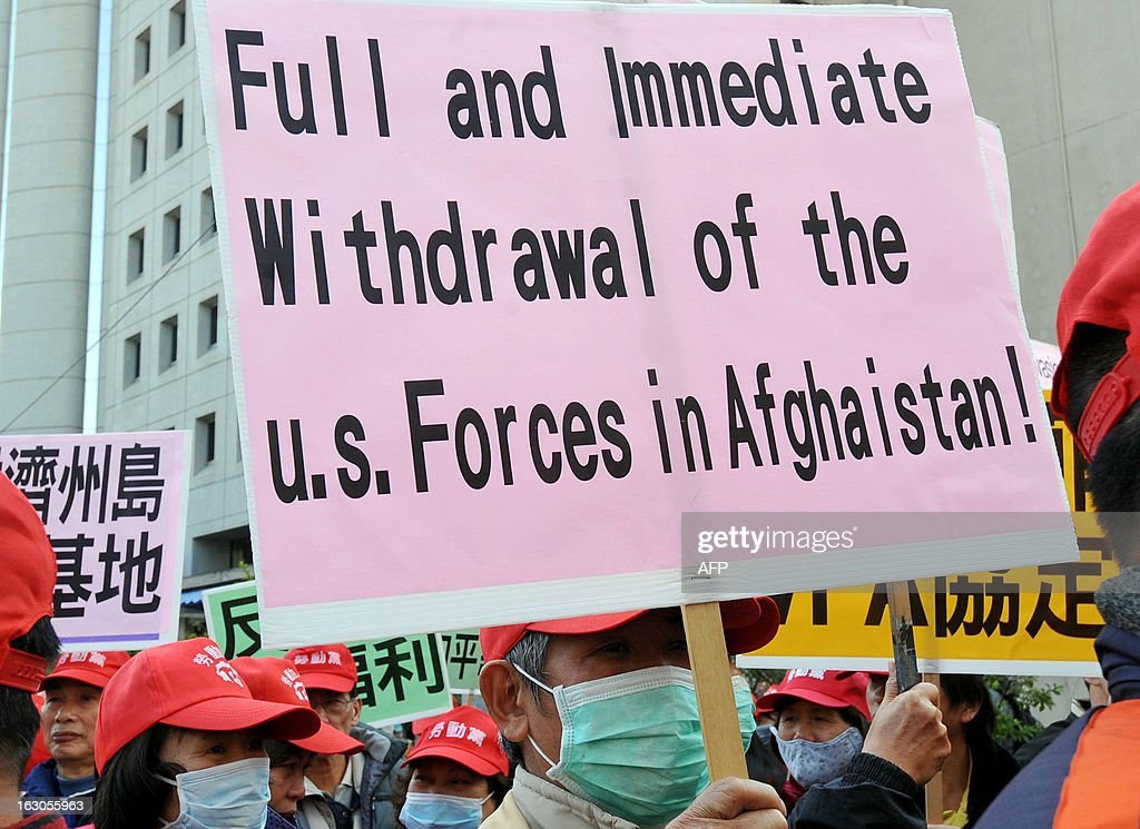 Demonstrators display placards during a protest in Taipei on March 4, 2013. Over 100 right-wing activists from Taiwan and five other nations demonstrated on March 4 at the de facto US embassy in Taipei urging a US military withdrawal from the Asia Pacific region. AFP PHOTO / Mandy CHENG