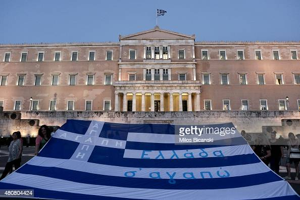 Demonstrators display the Greek flag in front of parliament on July 15 2015 in Athens Greece Antiausterity protesters hurled petrol bombs at police...