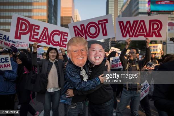TOPSHOT Demonstrators dressed as North Korean leader Kim JongUn and US President Donald Trump embrace during a peace rally in Seoul on November 5...