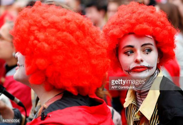 Demonstrators dressed as Ronald McDonald the mascot of US burger chain McDonalds as they participate in a protest over working conditions and the use...