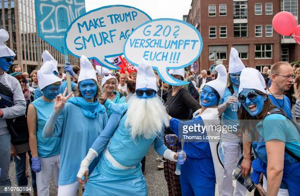 Demonstrators dressed as smurfs hold signs as they gather for 'Grenzenlose Solidaritaet statt G20' during a protesters march against the G20 Summit...