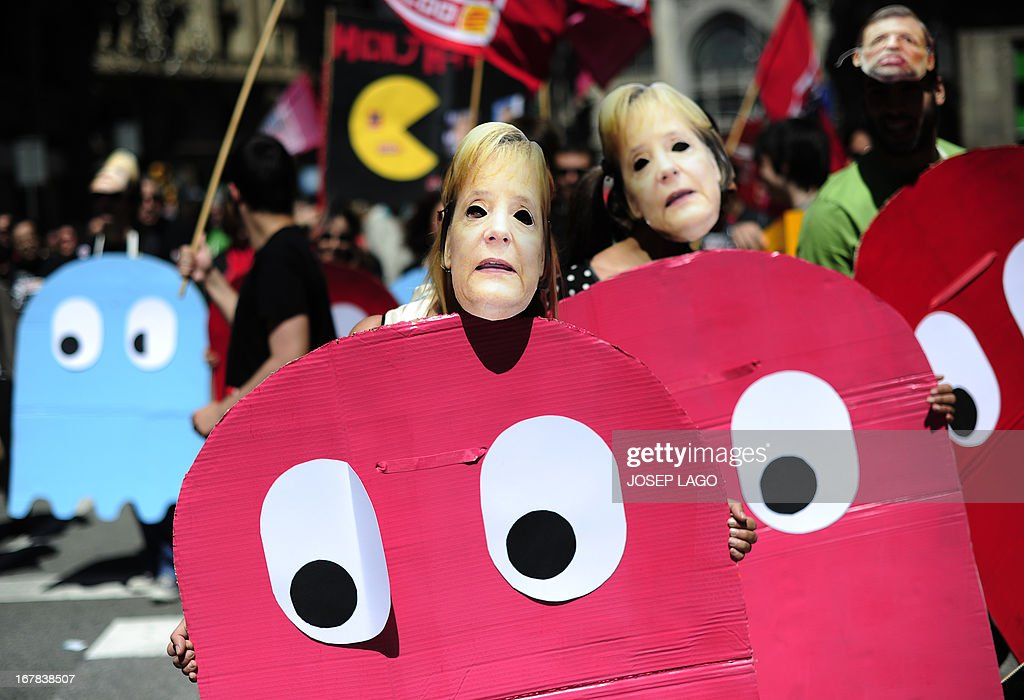 Demonstrators dressed up as characters of the video game Pac-Man and wearing masks of German Chancellor Angela Merkel, take part a Labour Day march against the Spanish government's austerity policies in the centre of Barcelona on May 1, 2013. Tens of thousands protested across the globe for May Day to press for workers' rights amid tough economic times and to back an array of other causes.