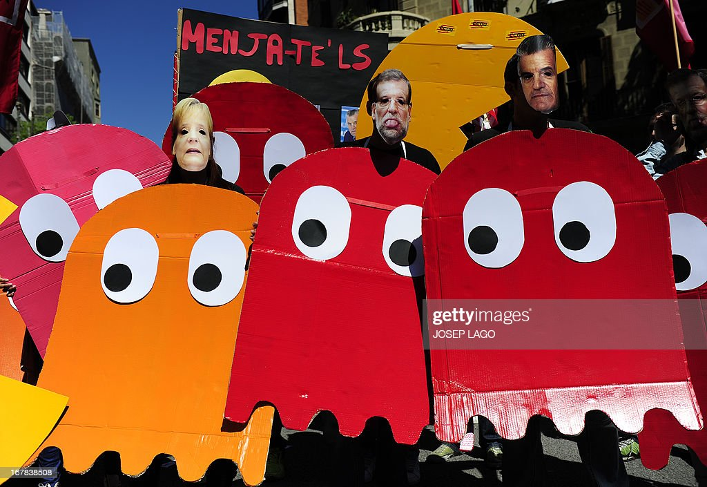 Demonstrators dressed up as characters of the video game Pac-Man and wearing masks of Spanish Prime Minister Mariano Rajoy (C) and German Chancellor Angela Merkel (L), take part a Labour Day march against the Spanish government's austerity policies in the centre of Barcelona on May 1, 2013. Tens of thousands protested across the globe for May Day to press for workers' rights amid tough economic times and to back an array of other causes.