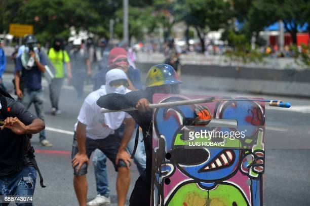 Demonstrators equipped with protective hardhats gloves and gas masks take cover behind homemade shields and aim a tube containing a firework during...