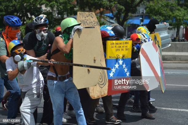 Demonstrators equipped with protective hardhats gloves and gas masks take cover behind homemade shields during clashes of opposition activists and...