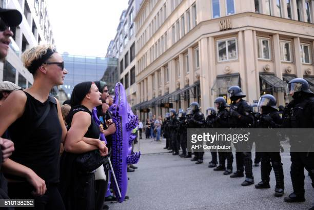Demonstrators face policemen during a protest on July 7 2017 in Hamburg northern Germany where leaders of the world's top economies gather for a G20...