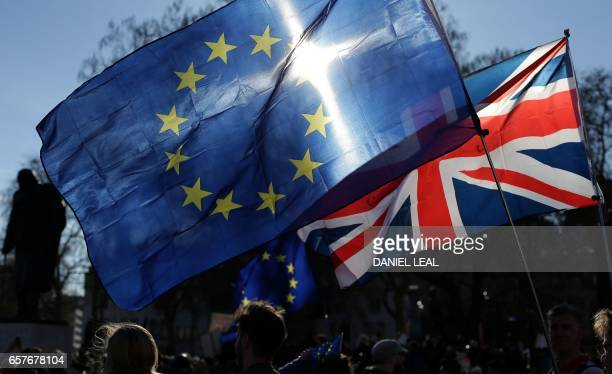 Demonstrators fly an EU and a Union flag during a rally following an anti Brexit proEuropean Union march in London on March 25 ahead of the British...