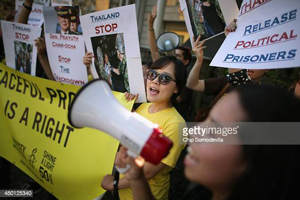 Demonstrators from Amnesty International rally against the military crackdown on opposition protests and free speech in Thailand outside the Royal...