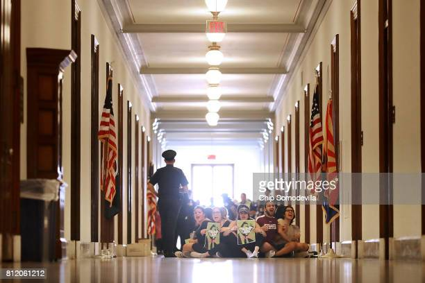 Demonstrators from Arizona chant 'Kill the bill or lose your job' while sitting on the floor outside the offices of Sen Jeff Flake during a protest...