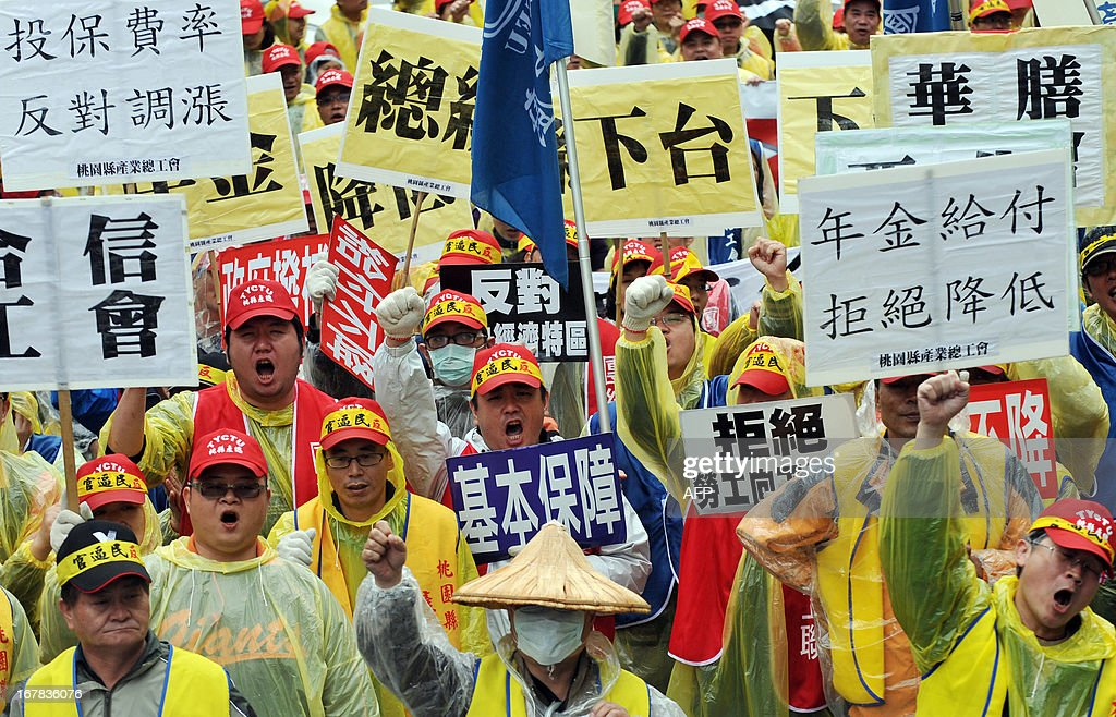 Demonstrators from labour unions chant slogans during a May Day rally in Taipei on May 1, 2013. More than 10,000 people took to the streets in Taipei to protest the government's planned pension cuts, including raising labour insurance fees and lowering the payment scale. AFP PHOTO / Mandy CHENG