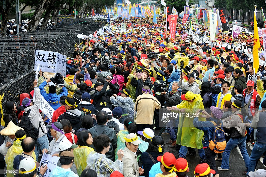Demonstrators from labour unions use ropes as they attempt to pull down barricades in front of the Executive Yuan building during a May Day rally in Taipei on May 1, 2013. More than 10,000 people took to the streets in Taipei to protest the government's planned pension cuts, including raising labour insurance fees and lowering the payment scale. AFP PHOTO / Mandy CHENG