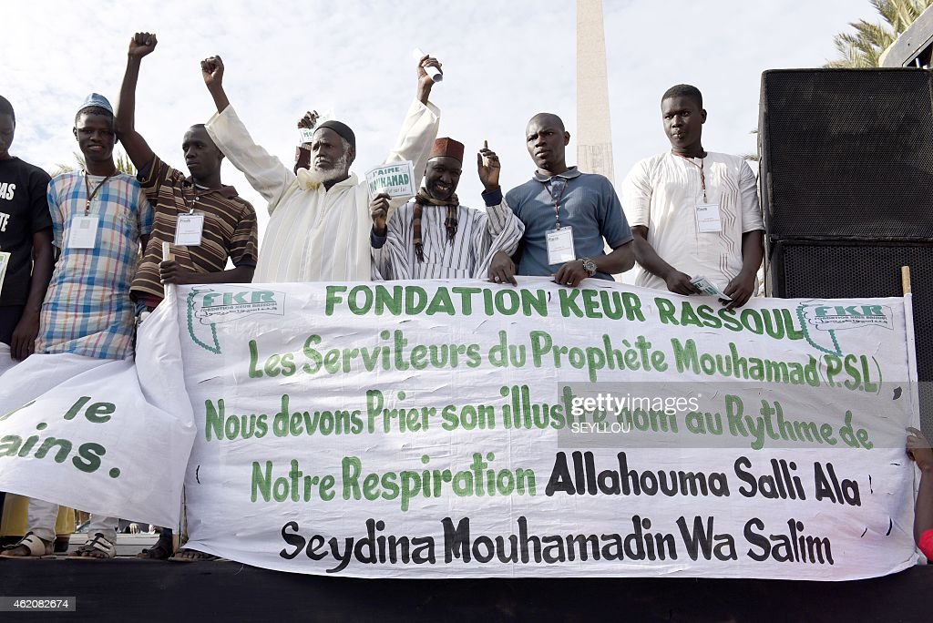 Demonstrators from the Keur Rassoul Islamic fondation hold placards which translates as 'I love Mohammed' in front of a banner featuring a Muslim prayer and a statement which translates as 'The servants of the prophet Mohammed. We have to pray his glorious name with every breath we take' on January 24, 2015 during a rally in Dakar to protest against French weekly Charlie Hebdo's publication of a cartoon of the Prophet Mohammed. AFP PHOTO / SEYLLOU