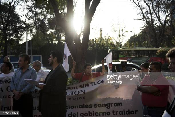 Demonstrators from the mine workers union hold flags and a banner during a protest ahead of the North American Free Trade Agreement renegotiations in...