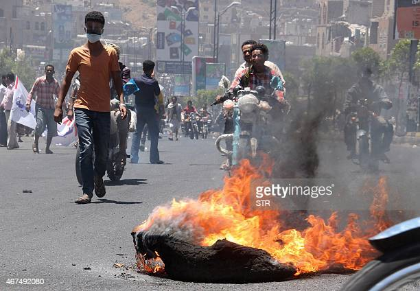 Demonstrators gather and burn tyres in Yemen's strategic city of Taez during a protest on March 25 against the Shiite Huthi militia's arrival in the...