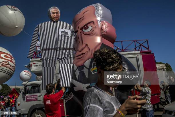 Demonstrators gather around inflatable figures in the likeness of Brazilian President Michel Temer during protests outside of the National Congress...