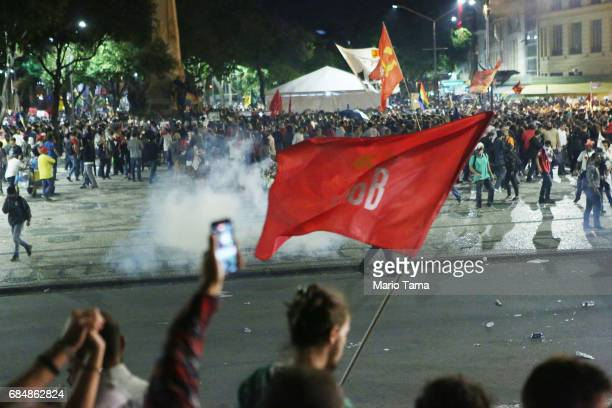 Demonstrators gather during an antiTemer protest as tear gas is launched on May 18 2017 in Rio de Janeiro Brazil Thousands of protestors hit the...