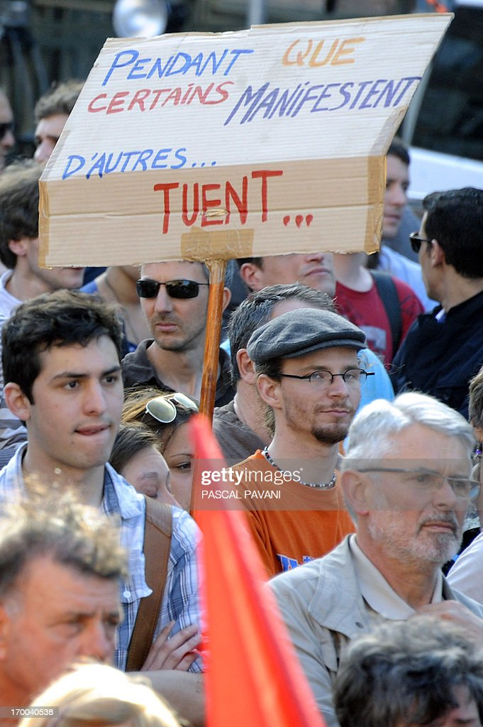 Demonstrators gather on June 6, 2013 in the southwestern town of Toulouse after a young far-left activist was killed during a fight with skinheads in central Paris. Clement Meric, an 18-year-old French far-left activist and student at the city's prestigious Sciences-Po university, died on June 6 following the fight. Clement Meric had been left brain dead after the violence on June 5. The police source said three men and one woman had been held and that the attacker who is thought to have dealt the fatal blow denied having an intention to kill. The board reads : 'While some demonstrate, others kill'.