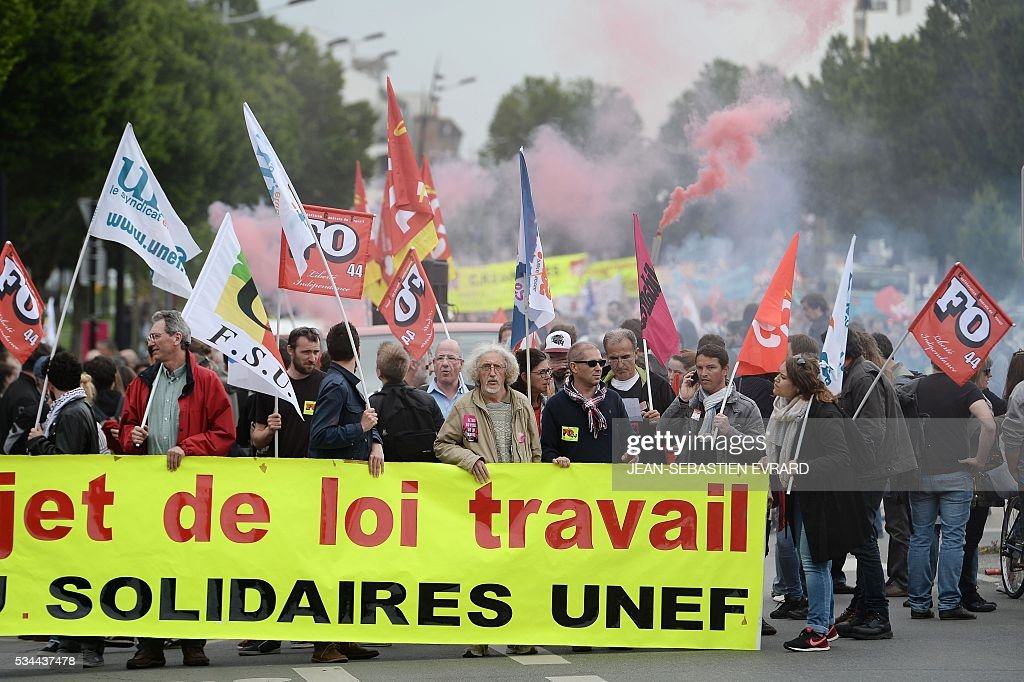 Demonstrators gather on May 26, 2016 in Nantes, western France, during a protest against government planned labour law reforms. The French government's labour market proposals, which are designed to make it easier for companies to hire and fire, have sparked a series of nationwide protests and strikes over the past three months. Masked youths clashed with police and striking workers blockaded refineries and nuclear power stations on May 26 as an escalating wave of industrial action against labour reforms rocked France. / AFP / JEAN